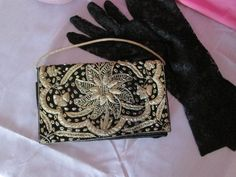 Vintage 1930's purse made from black velvet and goldwork embroidery, the embroidery is to the front and back of the purse with a gold cord handle. The purse has a simple flap and is secured with a press stud (snap) closure. The purse measures approximately 8 inches (20.3cm) wide by 5 inches (12.7cm) high, not including the handle. Overall the purse is in good used vintage condition; however, there are a few points to note: over time and use there is darkening to the goldwork on the right…