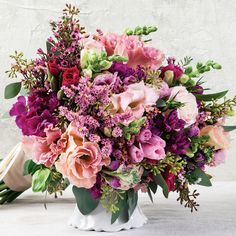 Lisianthus, sea lavender, godetia, snapdragon, and waxflower help create this gorgeous pink bridal bouquet.