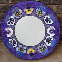 4 handmade ceramic pansies on round glass mosaic mirror. R2000.00