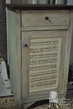 Mod Podge sheet music onto cabinet. Two bad she did the last two stanzas upside down. Whoops.