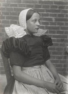 Meisje in Huizer streekdracht. Ze is tussen de 12 en de 16 jaar en draagt de daagse dracht. ze is gekleed in een jurk met pofmouwen, een 'lage schullek' (schort) en 'pikmuts' (gehaakte muts). 1916 #NoordHolland #Huizen #pikmuts