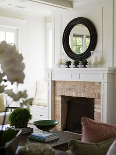 Cozy cottage living room with white wood and brick fireplace. Black, circular mirror hung above fireplace, glass hurricanes and trio of greenery. Great window seats flanking cottage fireplace with lots of natural light. White Mantle, White Fireplace, Fireplace Mantle, Fireplace Surrounds, Fireplace Design, Fireplace Ideas, Simple Fireplace, Shiplap Fireplace, Mantel Ideas