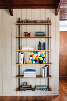 Wall-hung shelves at The Wood House, Carla and Niall Maher's midcentury ranch, an ongoing remodel/restoration project in Westchester, NY, photographed by Brian W. Ferry for Remodelista