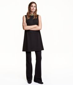 Short, sleeveless jersey dress with a beaded stand-up collar and concealed back zip. Unlined.