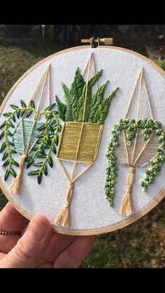 This 6 inch wooden hoop features a trio of hanging plants . Each one hanging in a hand stitched plant hanger , check out those tassels ! This is a made to order item and as such placement of leaves may vary slightly . The design really pops out from the hoop , I just love the texture that thread gives the plants . All my embroideries are designed and hand stitched by me here in Tasmania . I love making these stitchy gardens because who doesnt love a plant that is green all year round ! I…