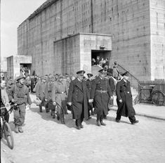 German prisoners, led by senior naval officers, are marched into captivity in Bremen, 26 April 1945. In the background is a huge reinforced concrete air-raid shelter.
