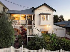 Weatherboard queenslander house exterior with balustrades & window awnings - House Facade photo 525957