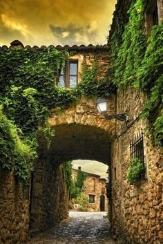 Cobblestone Arch, Girona, Spain    Breathtaking photo of a quaint cobblestone street and arch. beautiful example of the simplicity in some old Spanish architecture.
