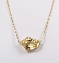 love the asymmetric cut on this yellow stone. gold and diamond pave