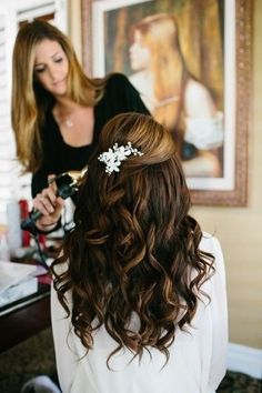 This hairstyle has full curls that is topped off with a barrette and pinned back hair. It is perfect for a dress that is very attention seeking in the front.