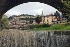 da sotto una briglia del fiume Crati il centro storico di Cosenza,visto attraverso un'arcata del ponte Alarico