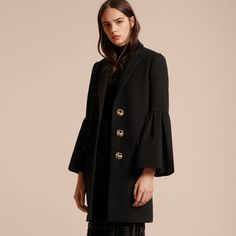 A deftly tailored Burberry coat cut from a fine wool and cashmere blend, with a smooth satin lining.