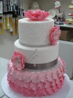 A 3 tiered pink ombre ruffled cake with gumpaste flowers with button centers and added bling.