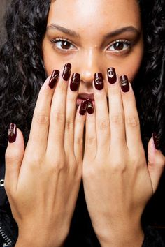 The look: Nail pro Jin Soon Choi designed seven different press-on looks using maroon, metallic gold, glossy black, and peach-beige polishes with metallic logo decals and graphic designs.  The kit: Marc Jacobs Hi-Shine Nail Polish in Blacquer, Ladies' Night, Gold Finger, TRAX, Moody, Oops.