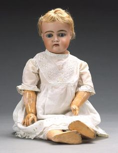 Kestner 192 bisque head doll, circa 1910 With weighted blue glass eyes, feather brows, open mouth, upper teeth and pierced ears, short blonde mohair wig and on a fully jointed fixed wrist composition body, wearing a white cotton dress, 61cm (24in) tall.
