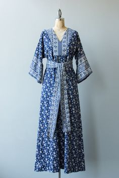 Vintage 1960s white and blue cotton maxi dress with floral print. This long boho dress has a low v-neck line, bell shaped sleeves and matching tie belt. Made by I. Magnin. Back metal zipper.  ✂ ✂ ✂ M E A S U R E M E N T S ✂ ✂ ✂  fits like: small to medium bust: 36 waist: free, unbelted hip: free sleeve length: 15 length: 54 brand/maker: I. Magnin, Ramona Rull condition: excellent  to read about our condition standards and read our sizing guide: www.etsy.com/shop/GoldBanana&#x2F...
