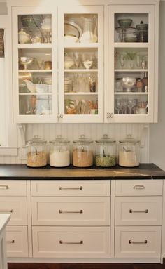 Antique window glass gets a new home in these cabinet doors, while glass storage jars lend a sense of continuity and organization to dry pantry goods.