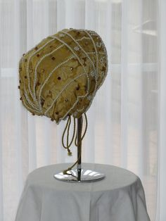 """Golden cap of silk brocade, following to paintings by Lucas Cranach. The dictum """"ALS IN EREN"""" written on the front band of the cap was the device of Sibylle of Saxony (1512-1554) and therefore also has been painted on her portrait by Lucas Cranach."""