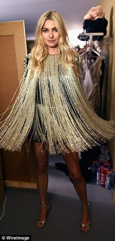 The 70s called, they want their look back! Jessica Hart arguably looked the most disco of them all in a black dress that possessed gold fringing along the front and rear to create a cape effect