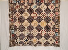 """c. 1840, 86 x 94, Ossing, NY area, fabrics dating  back t0 1810, block prints & calicoes in blue, yellow, madder, brown & tan - Ohio Stars 10"""" x 10"""" blocks set on point, 5"""" wide border of LeMoyne Stars, outer flying geese border is 3.25""""; hand pieced & quilted in diagonal & horizontal parallel lines using linen thread, back is homespun linen, 3/8"""" binding is brown calico."""