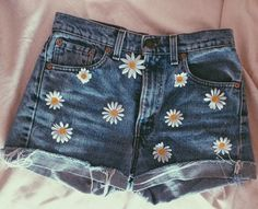 """Artificial Daisies hand sewn onto a pair of Vintage Levi High Rise 550 Shorts. Size 4 // 26 inch waist. Rise (Highwaisted part)- 11.5"""" Leg Openings- 20"""" One of a kind. Similar shorts sold at exclusive boutiques retail over $125! Please contact me if you have any questions!"""