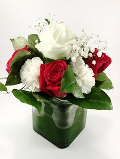 A small luminous red, white and green arrangement in a squared vase wrapped with with a natural leaf.