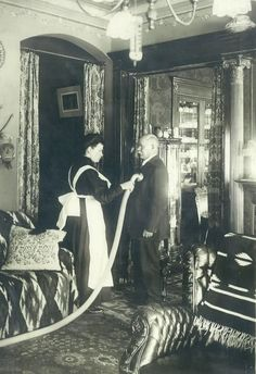 "Enoch invented a central vacuum system, and he's shown here ""getting his suit cleaned"" by one of the servants. This photo appeared in a manual on the central vacuum system that Tom and Barry found. It also shows great detail of the home's interior. This would have been a little after Addie's time, in the early 1910s."