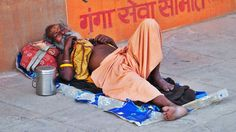 A sadhu taking a nap near the Dashashwamedh Ghat , Banaras (Varanasi), India