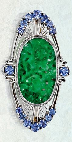 Louis Comfort Tiffany for Tiffany & Co. - An Arts and Crafts Platinum, Jade and Sapphire Brooch, 1915-1930. Centring an oval-shaped carved and pierced jade plaque of floral design, the openwork mounting decorated at the border with round sapphires, signed Tiffany & Co.