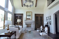 Greenwood King Properties | Houston Real Estate | This stunning family room features a beamed cathedral ceiling, soaring windows, hand-carved limestone mantle with Isokern fireplace, wide-plank oak floors, and fabulous custom built-ins.