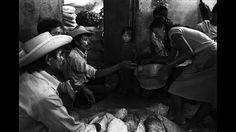 """Foto correspondiente a la exposición """"Desarraigos"""". Los años '80, estuvieron llenos de mucho terror, sin embargo yo aprendí de los salvadoreños en departamentos como Chalatenango y Morazán, entre otros lugares, el valor de la solidaridad, la paciencia y el hacer el trabajo como se hace en un hormiguero: con constancia, disciplina y en apoyo mutuo"""". En la imagen, un grupo de campesinos desplazados del norte del país, de Chalatenango, comparten unos granos para pasar el hambre."""