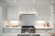 Lovely white kitchen features white shaker cabinets paired with white marble countertops and ...