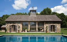 Designed by architect Gil Schafer, decorated by John Cottrell, and landscaped by Deborah Nevins, a Connecticut poolhouse takes the shape of a sophisticated barn with stone walls and weathered plank shutters. The custom-made windows are by Reilly Windows & Doors.