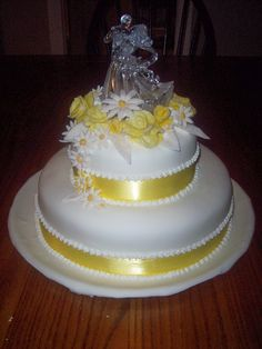 2 tiered white and yellow wedding cake with daisy accents.