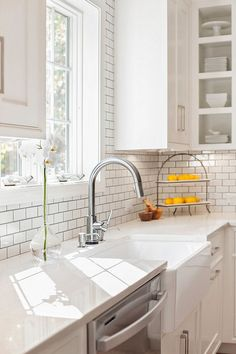 Farmhouse sink with Misty Carrara Caesarstone quartz countertop and subway tile backsplash. New England Design Works