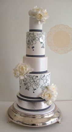 White and navy blue cake, with outlined floral design, pearl finish, big white sugar blooms, and can you see the metallic finish little birds? Pretty!