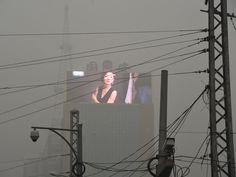 an electronic billboard through a screen of pollution in Beijing, China