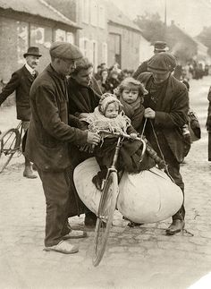 First World War: Man holding a heavy loaded bicycle in balance, two children and a large bundle of clothing on it, a woman and an other man helping. The children warmly dressed. Refugees from Antwerp. Belgium, 1914.