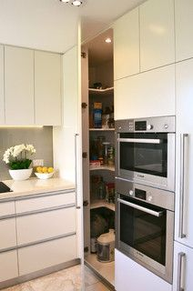 Corner pantry with door flush with cabinetry. Wall with fridge and wall oven