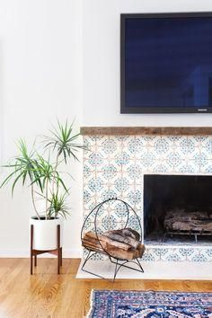 Love these blue and white printed Spanish tiles around the fireplace paired with midcentury living room accents for a modern, global-inspired look.