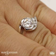The Mark Schneider Escape Solitaire Engagement Ring is sure to add a bit of whimsy to your day to day. The bezel set center diamond is accented with 3 channel set Round Brilliant Diamond Melee (0.115ctw; F/G VS) which graduate in size. The look is finished off by the signature Round Brilliant Diamond Melee (0.005ctw; F/G VS) nestled within the <a href='http://www.whiteflash.com/about-diamonds/jewelry/mark-schneider-secret-heart-1384.htm'><u><b>Secret Heart</b></u></a>. The width tapers from…