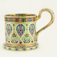 A Russian gilded silver, plique-à-jour, and champlevé enamel tea glass holder, 11th Artel, Moscow, 1908-1917. Decorated with scrolling Neoclassical forms in champlevé, the upper rim with leaf motifs in translucent red, blue, yellow, and green plique-à-jour enamel motifs.
