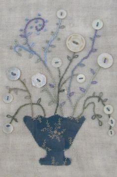 Vintage mother-of-pearl buttons, hand appliqued blue urn with tiny flowers, hand embroidery on vintage linen.