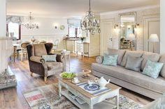 Salon połączony z jadalnią został urządzony z przepychem, pełnym bibelotów i dekoracyjnych form. Bielony stolik kawowy z pojemnymi szufladami z kutymi uchwytami otaczają eleganckie meble o barokowych kształtach, w szarości i brązie. Spore wnętrze rozświetlają kryształowe żyrandole. Tonacja wnętrza jest stonowana, oscylująca wokół beży, szarości, błękitu.