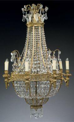 Lustre corbeille à huit lumières en bronze ciselé et doré, les bras en forme de torches rubanées. Il est rehaussé de pendeloques, amandes, feuillage de cristal moulé et taillé. Style du XVIIIe siècle.