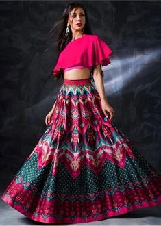 A multicoloured lehenga with abstract print in the shades of turquoise blue and fuschia pink. Moreover, teaming it with a unique cape-style hot pink blouse gives the outfit a perfect finishing. Hot Pink Lehenga with abstract print Indian Gowns Dresses, Indian Fashion Dresses, Dress Indian Style, Indian Designer Outfits, Fashion Outfits, Indian Wear, Trendy Outfits, Lehnga Dress, Lehenga Choli