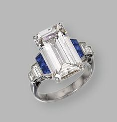 PLATINUM, DIAMOND AND SAPPHIRE RING The emerald-cut diamond weighing 7.03 carats, flanked by baguette diamonds weighing approximately .40 carat, and French-cut sapphires