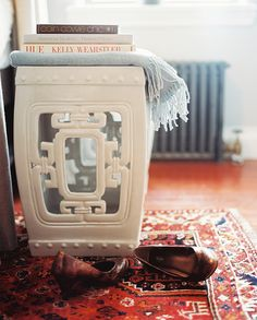 Ellie Somerville Photo - A white garden stool atop a patterned carpet
