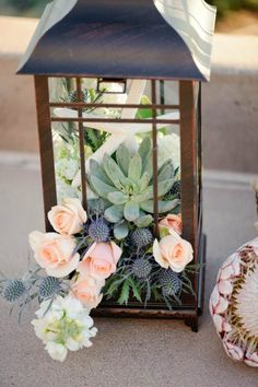 lanterne en métal patiné remplie de succulentes, roses et chardons