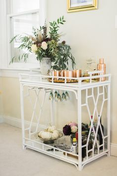Rose gold accessories on white bar cart